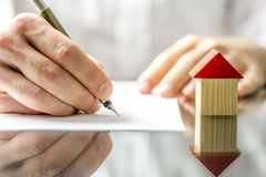 Man signing a contract when buying a new house. Conceptual image of a man signing a mortgage or insurance contract or the deed of sale when buying a new house or
