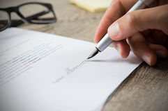 Man signing contract. Close up of hand of businessman signing a form. Business man signing contract for future deal. Business man signing legal document. Male royalty free stock image