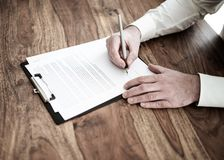 Man signing contract or document at wooden desk royalty free stock photos