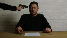 Man signing contract at gun point of woman stock footage