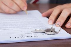 Man signing contract with keys on it Royalty Free Stock Images