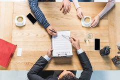 Man signing contract. Overhead view of man signing contract at table during meeting with lawyer Stock Image