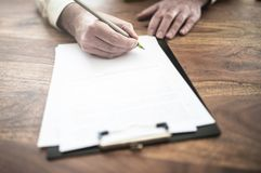 Man signing contract at wooden desk stock images