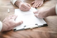 Man signing contract at wooden desk with other person pointing at document. Close-up of man signing contract at wooden desk with other person pointing at stock photo