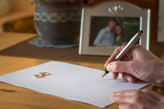 Man signing divorce. Man signing document. Golden rings. family picture background Stock Image