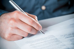 Man signing a document with a fountain pen Stock Photography