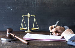 Man signing document with gavel and justice scale. Man signing document with gavel  and justice scale Stock Images