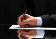 Man signing a document or writing correspondence with a close up view of his hand. With the pen and sheet of notepaper on a desk top Stock Images
