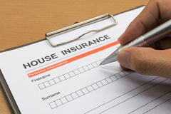 Man signing a house insurance policy Royalty Free Stock Photos