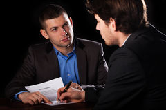 Man signing a loan with a lawyaer. A client signing a loan agreement with his lawyer stock image