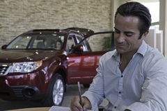 Man signing papers with car in background Stock Photos