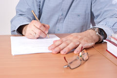 Man signing papers and contracts on the table. Man signing papers on the table. Focused on the hand holding a pen Stock Photography