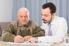 Man signing papers at home Royalty Free Stock Image