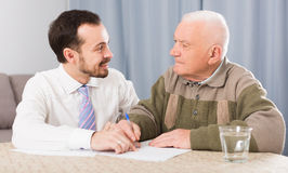 Man signing papers at home Royalty Free Stock Photos