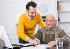 Man signing papers in office. Old male client signing agreement papers in office with manager Stock Images