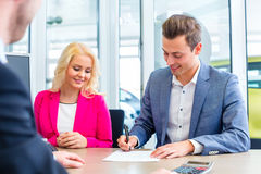 Man signing sales contract for auto at car dealership stock photos