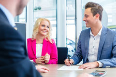 Man signing sales contract for auto at car dealership Royalty Free Stock Images