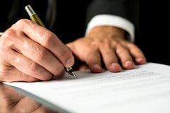Man signing a typed document Royalty Free Stock Images