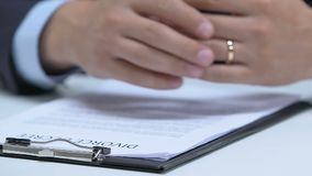 Man signing up divorce degree, taking off engagement ring from finger, break-up. Stock footage stock video footage