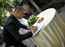 Man signing wedding papers. While bride looks on Stock Photos