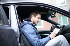 Man signs a document while sitting in the car stock photo
