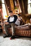 Man siiting på soffan som spelar videospel, hans hund som nästan sitter honom Fotografering för Bildbyråer