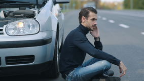 Man siitting near broken car and calling for help. Road trip car trouble. A young man with a silver car that broke down on the road stock footage