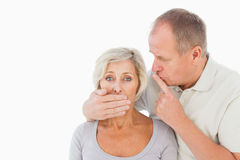 Man silencing his fearful partner Royalty Free Stock Photo