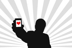 Man silhouette. A young man silhouette with a phone which has an isolated red heart figure inside Royalty Free Stock Photography