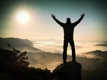 Man silhouette climbing high on cliff. Hiker climbed up to peak enjoy view. Stock Images