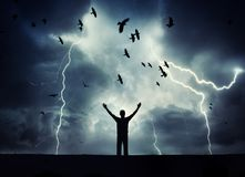 Man silhouette on a storm background. Lord of the lightning. Background on the theme. Man silhouette and crow on a storm background. Lord of the lightning royalty free stock photo