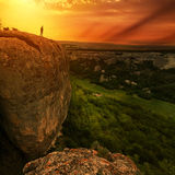 Man silhouette on edge of rock Stock Image