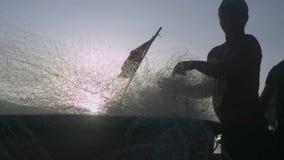 Man Silhouette Folds Net into Boat after Storm Closeup. NHA TRANG/VIETNAM - NOVEMBER 07 2017: Closeup man silhouette folds fishing net into round boat with flag stock video