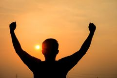 Man silhouette holds up his arms fist. As the winner at sunset Stock Image