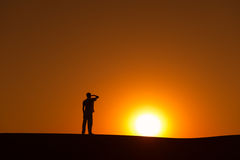 Man silhouette on horizon looks ahead. To gold sunset sun on orange and yellow sky Royalty Free Stock Photos