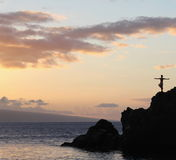 Man Silhouette. An inspiring image of a silhouette of a man standing on the rocks edge at the ocean stock images