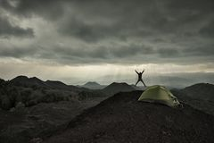 Man silhouette jumping under dramatic sky on volcanic landscape by wild camp in Etna Park royalty free stock photography