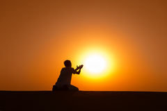 Man silhouette kneel and pray for help. With gold sunset sun on background Stock Photos