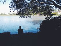 Man silhouette on lake stock photos