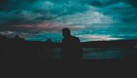 Man Silhouette Near Body of Water at Nighttime Stock Image