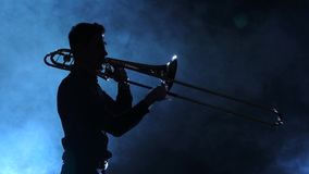 Man in silhouette playing on trombone. Smoky studio, slow motion stock video footage