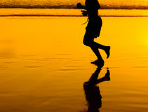 Man silhouette running on golden beach Stock Image