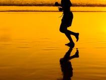 Man silhouette running on golden beach Stock Image