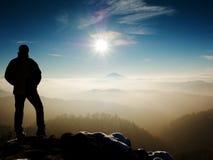 Man silhouette on sharp peak. Satisfy hiker enjoy view. Man silhouette stay on sharp rock peak. Satisfy hiker enjoy view. Tall man on rocky cliff watching down Stock Photo