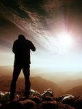 Man silhouette on sharp peak. Satisfy hiker enjoy view. Man silhouette stay on sharp rock peak. Satisfy hiker enjoy view. Tall man on rocky cliff watching down Royalty Free Stock Image