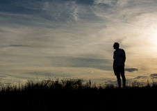 Man in silhouette. Standing on hill contemplating life and enjoying the view Stock Photos