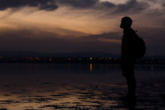 Man silhouette, standing on the lake and contemplating a beautiful sunset. Royalty Free Stock Photo