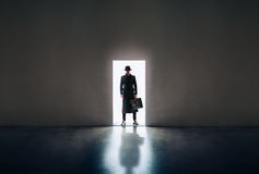 Man silhouette standing in the light of opening door in dark roo. Man silhouette in hat and raincoat standing in the light of opening door in dark room Stock Images