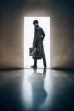 Man silhouette standing in the light of opening door in dark roo. Man silhouette in hat and raincoat standing in the light of opening door in dark room Royalty Free Stock Images