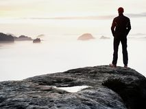 Man silhouette stay on sharp rock peak. Satisfy hiker enjoy view. Tall man on rocky cliff Stock Images